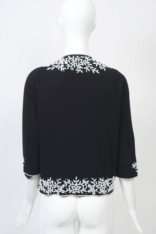 Black wool knit cardigan with white foliate beading around borders and decorating the three-quarter length sleeves. Edges bound in white satin, as are side slits, which can be hooked closed. Lined.