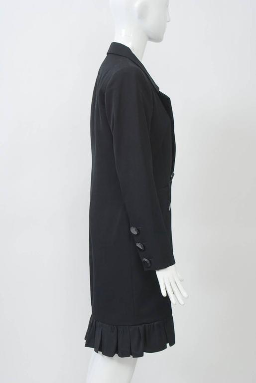 Black tuxedo-style coat dress with satin lapels and large jet buttons down front and at wrist. Satin ruffle at knee-length hem curves up at front. Shaped body with horizontal pockets.  Square shoulders with pads. Lined.