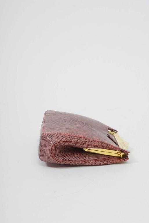 Beautiful dusty rose color and interesting markings distinguish this clutch from Judith Leiber that has a Deco-style goldtone frame and clasp. Matching narrow strap converts the clutch to a shoulder bag. Interior contains Leiber accessories - mirror
