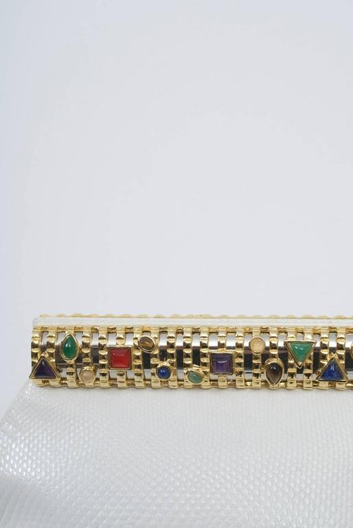 White karung clutch by Judith Leiber featuring a jeweled frame rectangular goldtone frame. Narrow karung strap converts the clutch to a shoulder bag. Interior with side compartments and Leiber accoutrements, concluding mirror, comb, and change