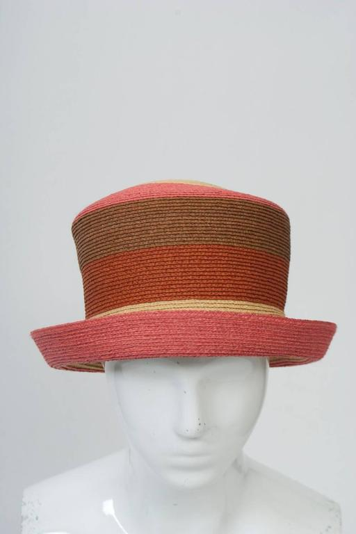 Australian designer Annabel Ingall hat in bands of natural, melon, rust, and brown straw. High crown with small, turned-up brim. Looks unused.