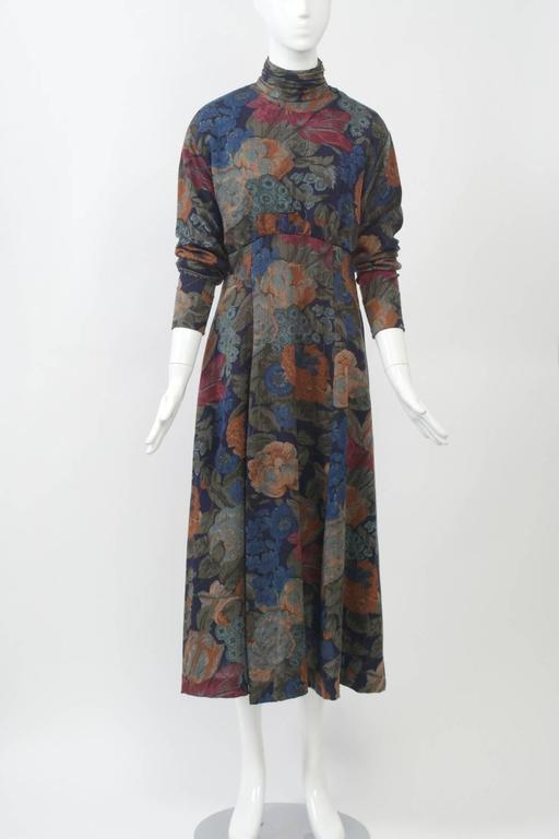 Wool challis mid-calf dress in a subtle floral print features a high waistline, dolman sleeves and a gathered turtle neckline. Finishing touches include tiny buttons in loops down the back and at the tapered wrists. There is also a side zipper. The