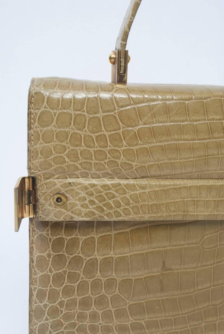 Great size and neutral color define this alligator handbag featuring gold metal clasps on either side of the envelope flap. The single handle is fastened with similar metal braces. On the beige leather interior, there are multiple pockets, including