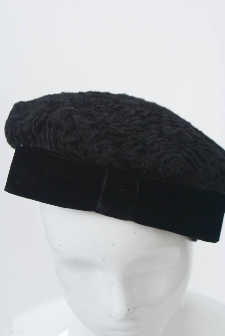 Black broadtail beret trimmed with velvet band and bow. Retailed by Bonwit Teller.