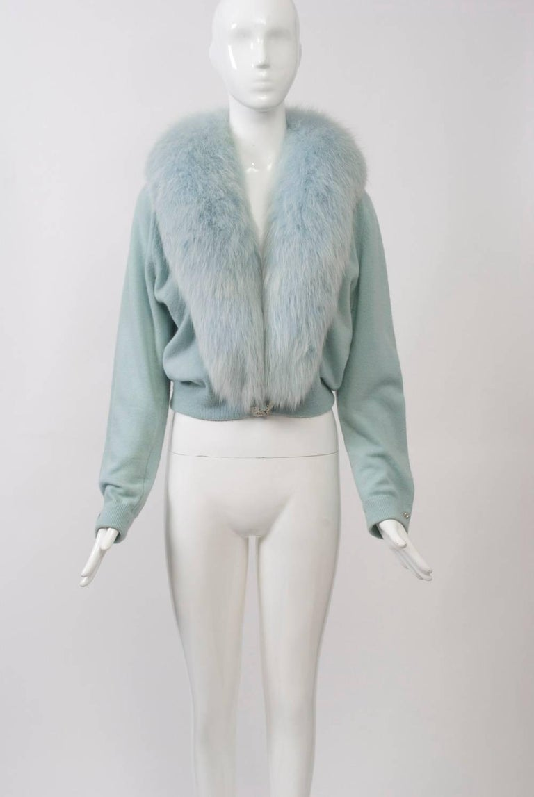 A special example of the decorated and/or fur-trimmed cashmere sweaters that were so popular in the 1950s and '60s, this cardigan is in baby blue with a matching full fox shawl collar. It is further enhanced with a rhinestone clasp at the waist and