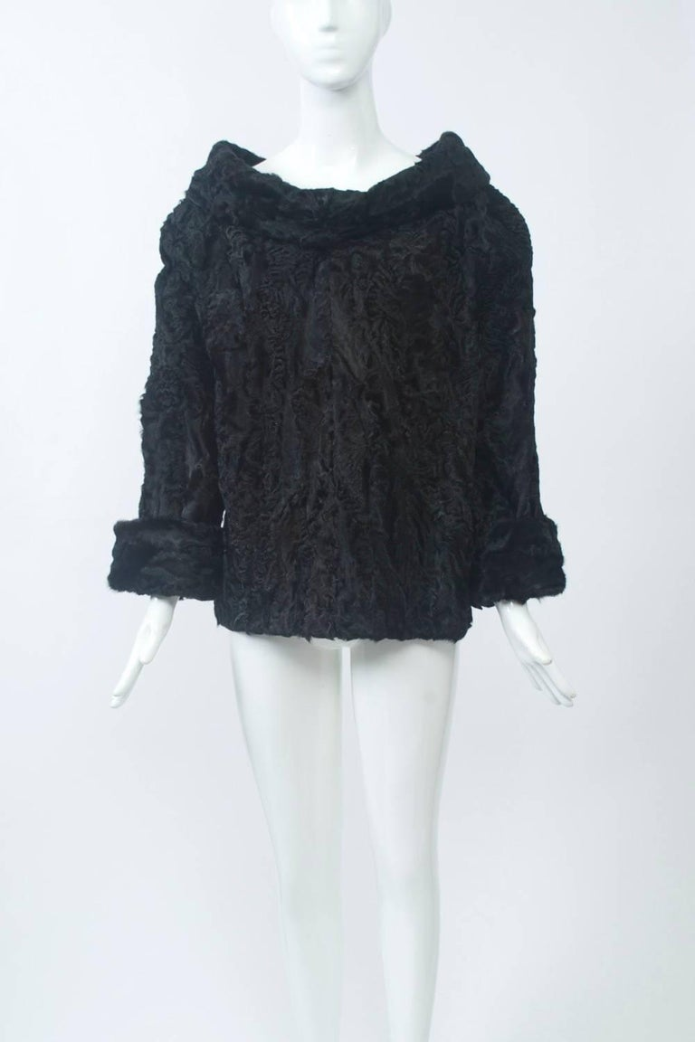 Black broadtail, custom-made tunic featuring a wide cowl collar and turned back cuffs. Slips over the head. A truly unique piece to pair with anything from jeans to a long skirt or more formal pants. Approximate size Small.