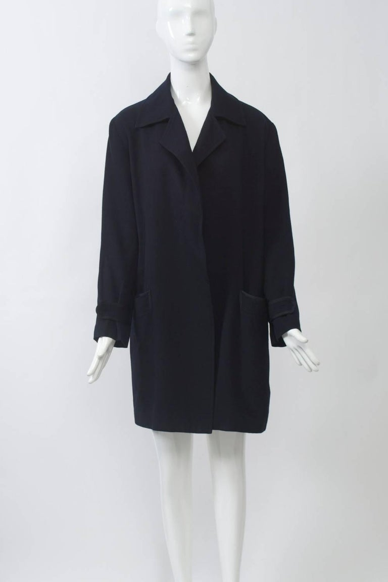 Long jacket in soft navy gabardine that feels like cashmere (the contents label is worn). Notched collar, loose fit, with flat braided trim on pockets and wrist tabs. Yoke back with deep inverted pleat. No closures. Size S-M.