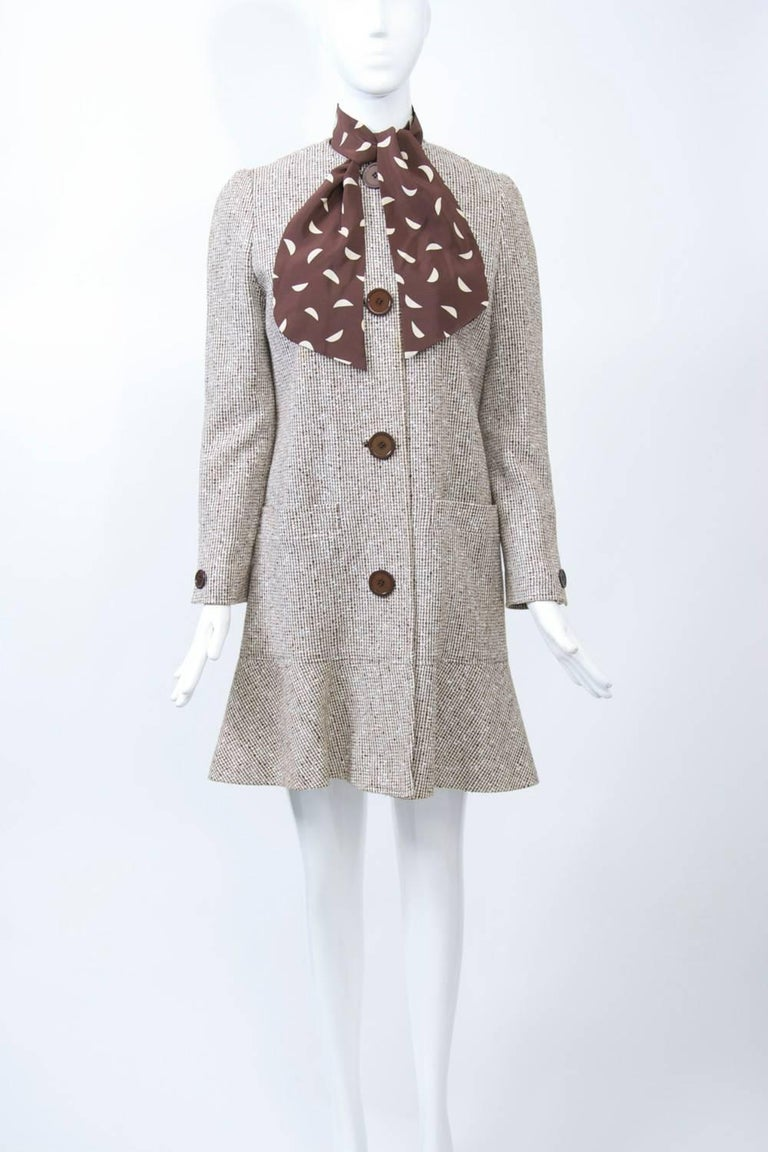 Coat and dress ensemble by David Hayes, a Los Angeles designer known for his timeless ensembles and dresses and who counted among his famous clients Nancy Reagan. The coat is fashioned of a brown tweed in a linen or cotton blend and features a deep