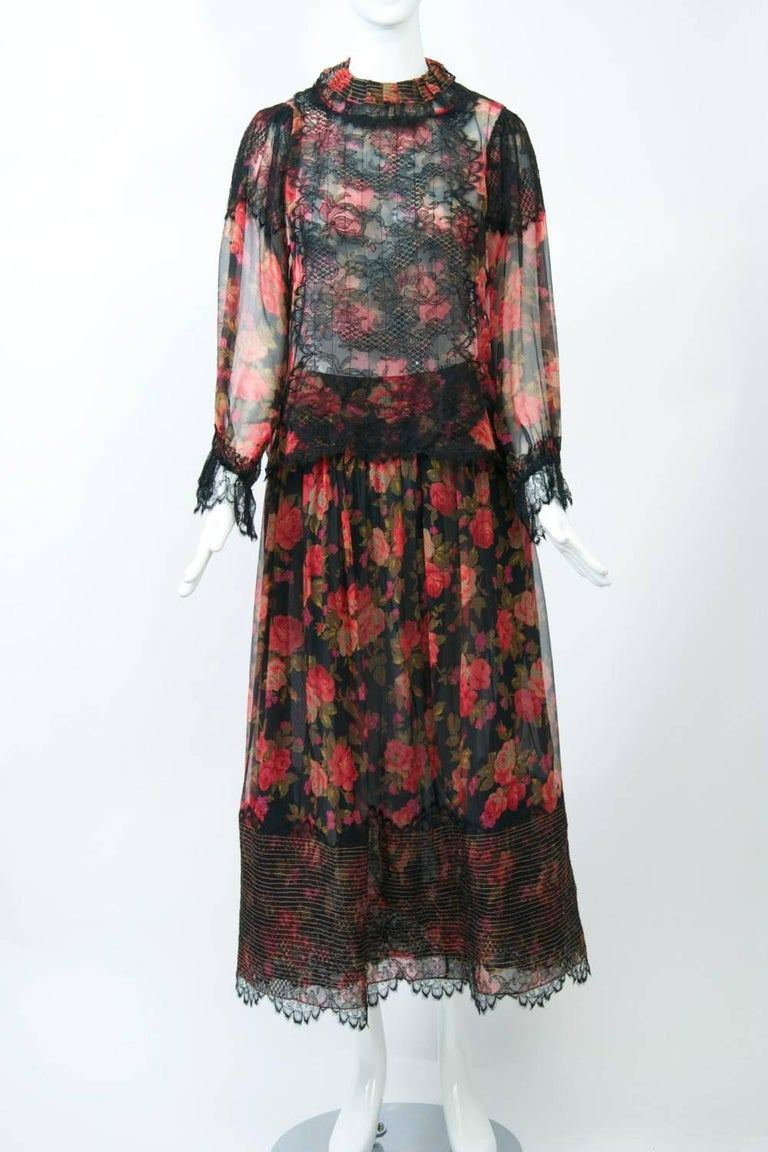 c. 1990s iconic Geoffrey Beene evening ensemble composed of silk chiffon with a red floral print on a black ground; the chiffon is overlaid with black lace accents. The top features a high neck with pleated and stitched pirouette collar trimmed in