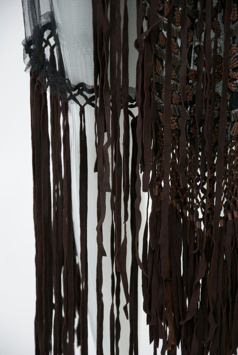 A vintage Fendi piece, c.1970s, composed of an interesting mix of materials. The overskirt features black net suspended from a denim hip band; below the netting is brown suede fringe that descends to the ankles. The centerpiece is a matching fringed