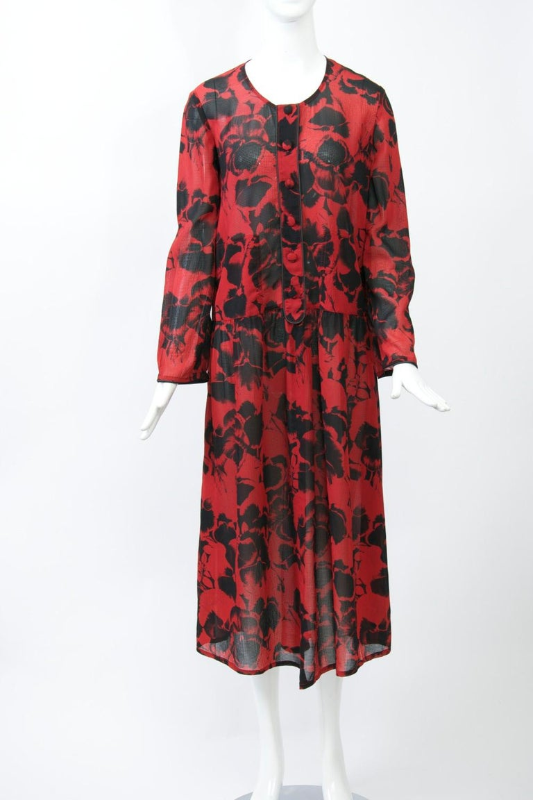 c.1980s Sonia Rykiel loose-fitting dress with a dropped waist in a sheer black-on-red floral print. Features include a round neck and a buttoned placket in front; placket and wrists trimmed in black piping. Soft, gathered skirt from hip.