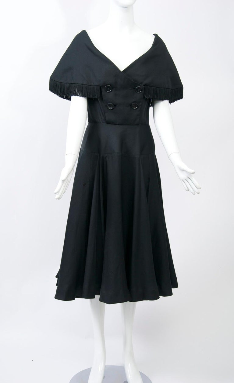 Jacques Fath designed two lines of ready-to-wear per year for NY manufacturer Joseph Halper from 1949 through the mid 1950s. This black dress features some outstanding details, from its fringed cape collar and decolletage neckline to its