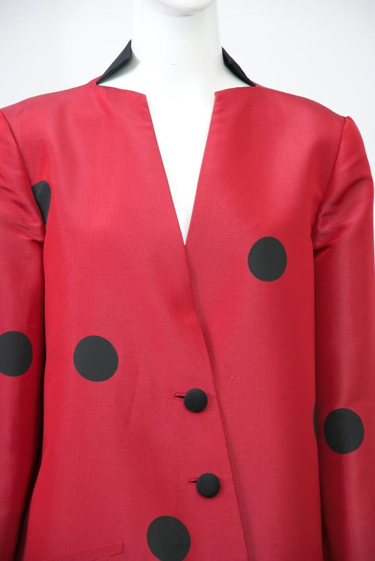 Typical of design master Geoffrey Beene, this suit exhibits the deceptive simplicity and attention to detail for which he was known. The silk jacket is fashioned of deep red silk with large black dots widely interspersed throughout. It has an