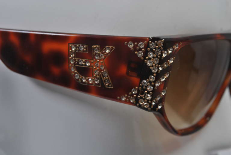 Beautifully shaped sunglasses from Emanuelle Khanh in tortoise plastic with rhinestone decoration at sides and logo. Straight edge across top and soft angles at bottom of lenses, wide arms that taper towards ear. Made in France.