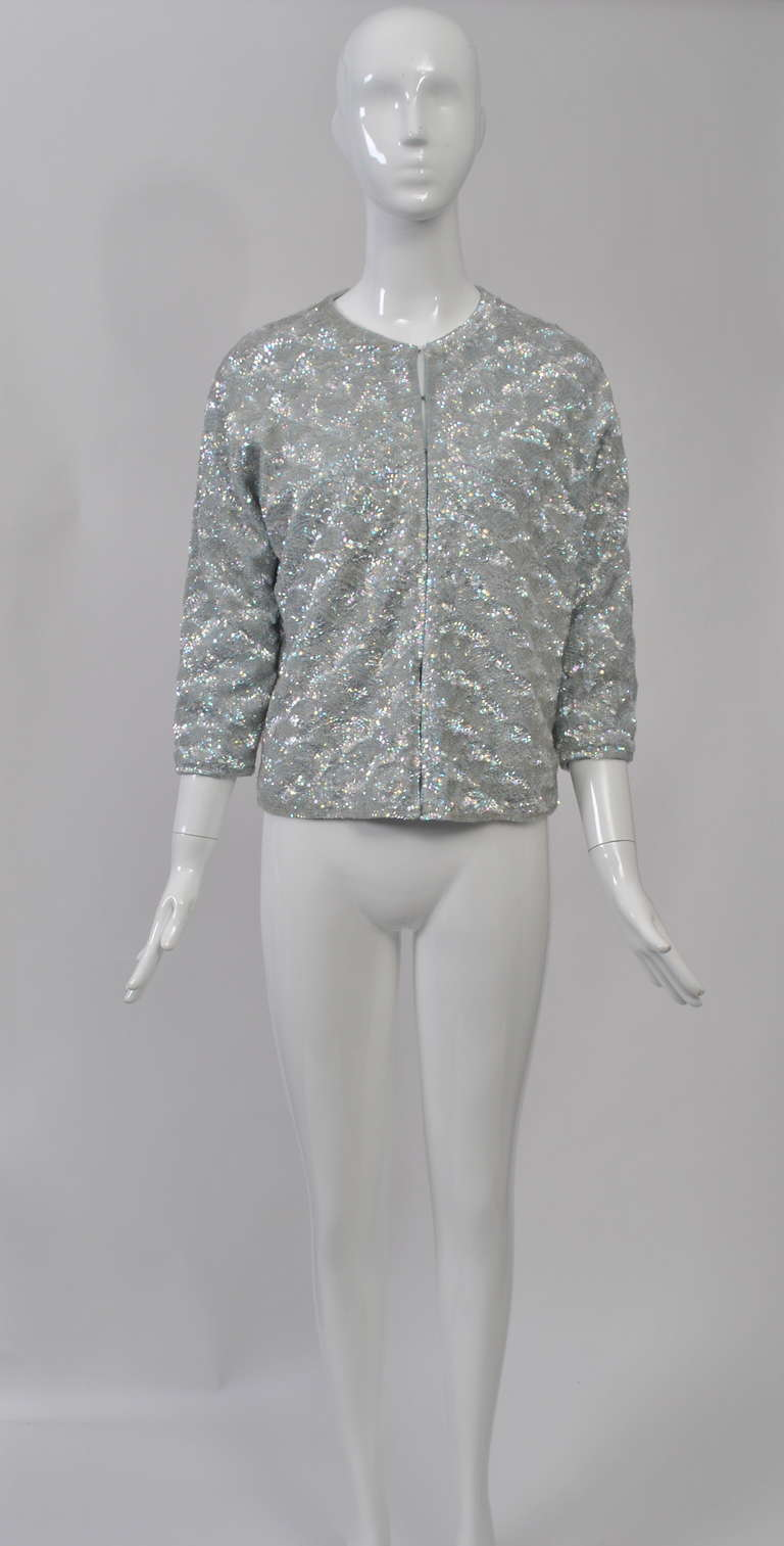 The decorated sweaters from the 1950s-'60s are always perfect vintage buys. This example is a knit cardigan decorated in an allover fan pattern of pale blue iridescent sequins, great for this time of year. Hooks and eyes down the front, 3/4 sleeves,