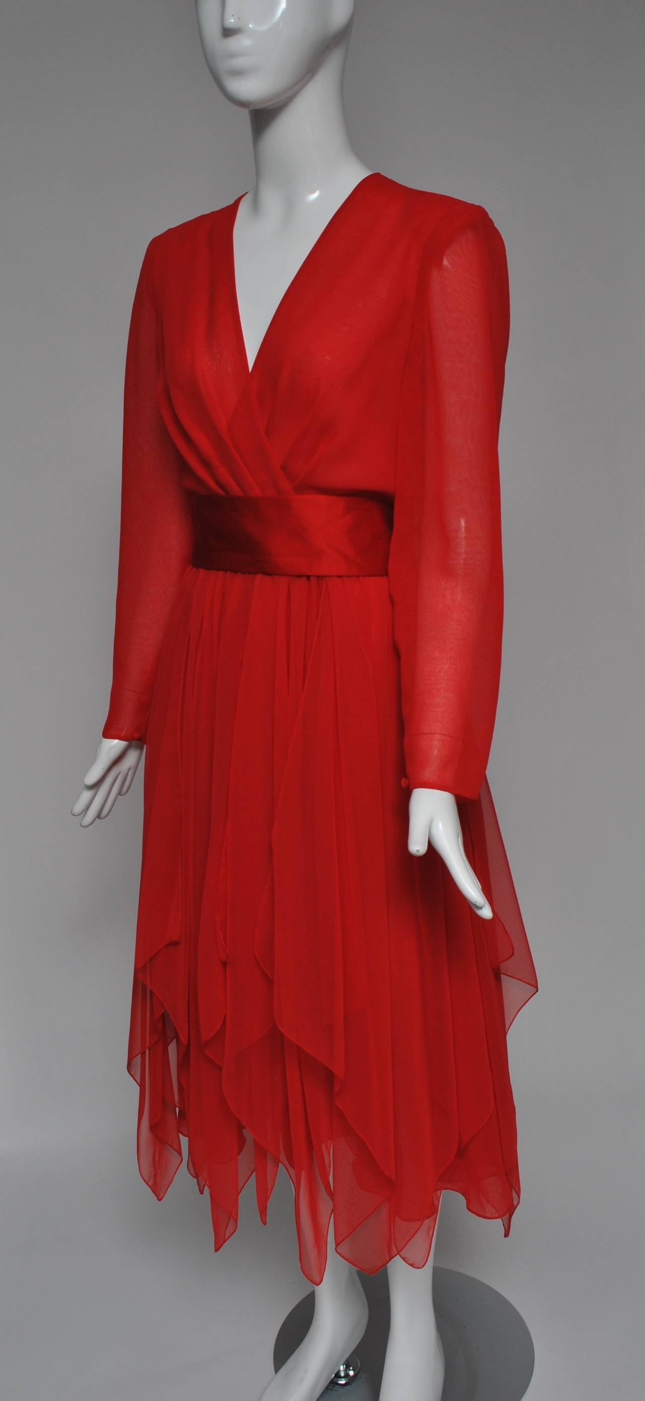 Late 1970s red cocktail dress in polyester chiffon by Estevez features a surplice top and handkerchief-paneled skirt. The long sheer sleeves button at the wrist. A wide red satin sash wraps around the waist and ties in back with long streamers.
