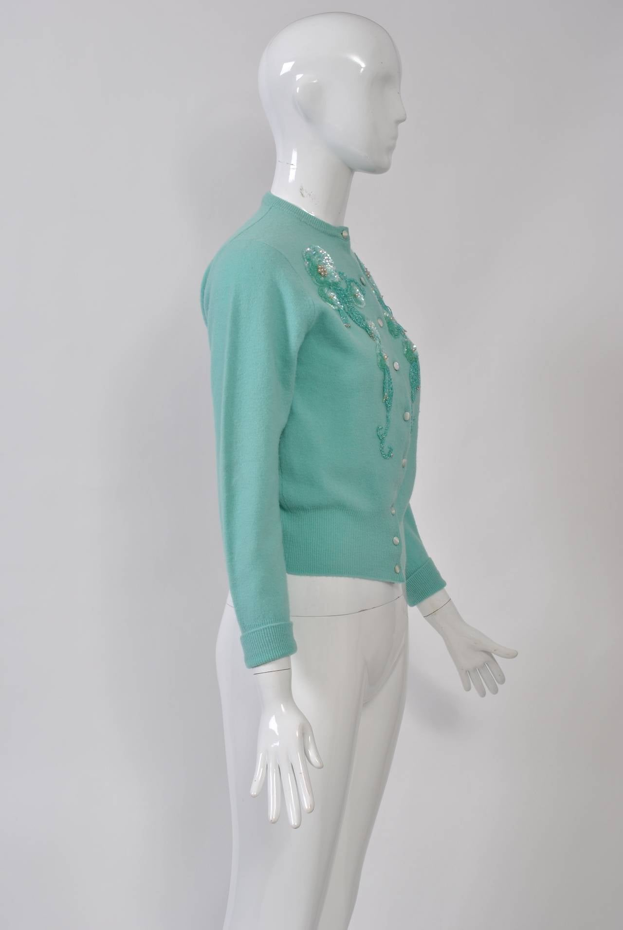 Among our favorite vintage pieces are the decorated cardigans from the 1950s-'60s. This example is in a beautiful shade of aqua and is embellished with matching beads and sequins. Unlined. Small size.