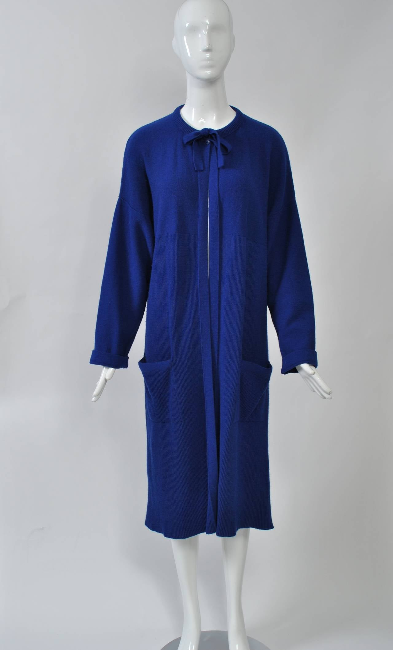 Typical Rykiel styling in this sweater coat of royal blue knit wool with tie neckline, dropped shoulders, and patch pockets. Bodice is plain knit, below is narrow ribbing.