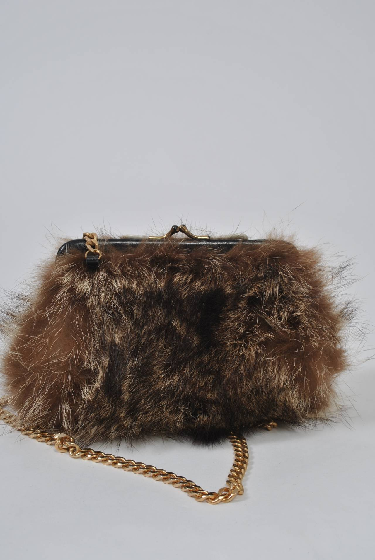 "Small shoulder bag in fur, probably raccoon, with black leather frame and long gold chain. Black interior. Unmarked. Chain length: 37""."