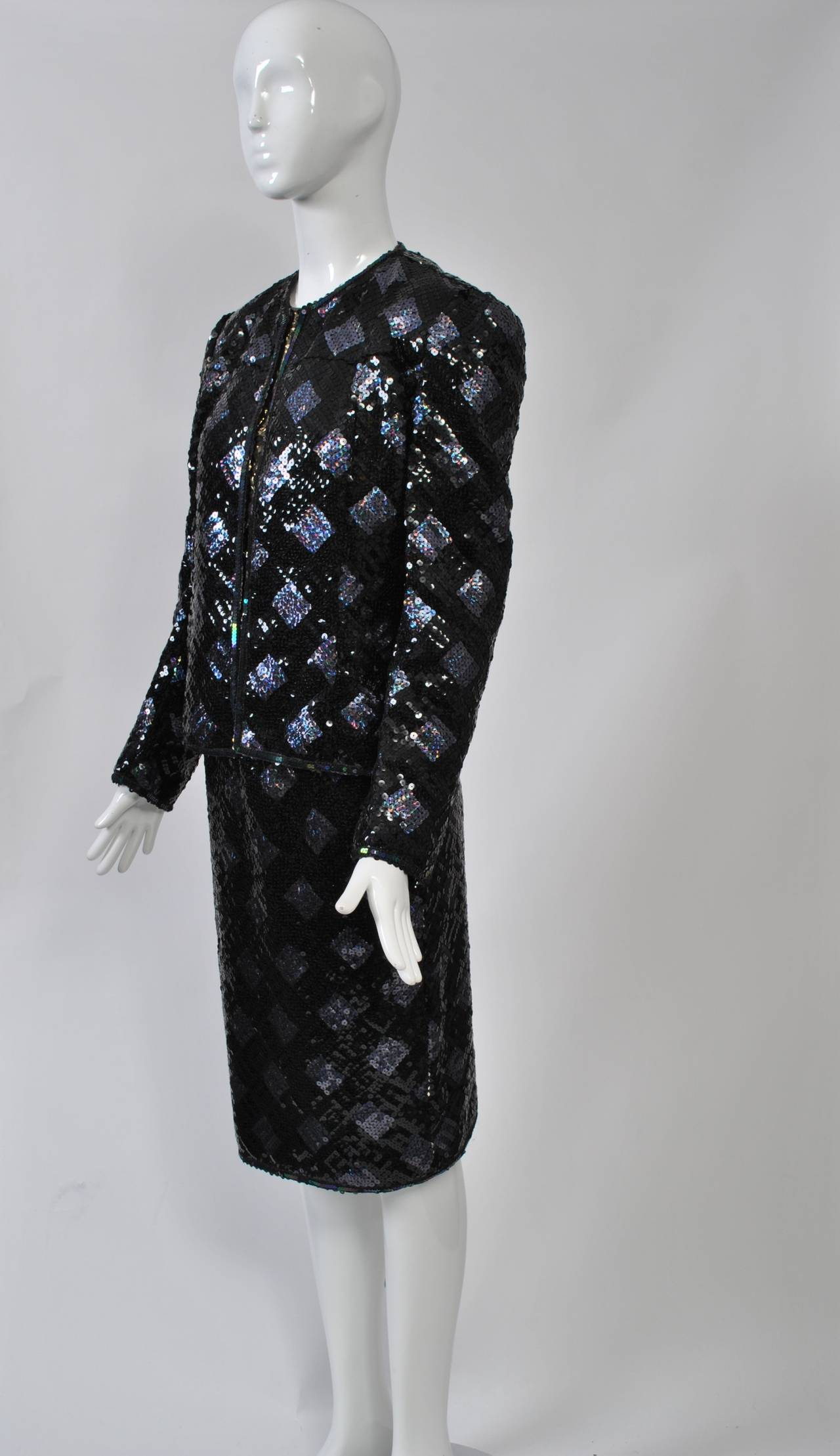 Three-piece evening suit by Adolfo, the slim skirt and collarless jacket in diamond-patterned black and iridescent sequins. The sleeveless shell is made of a krinkle metallic gold fabric, as is the lining of the jacket and the waistband of the