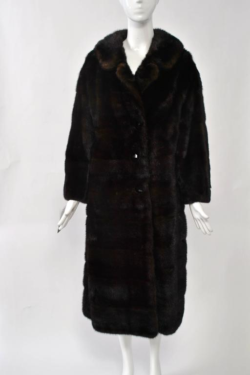 1960s-'70s mahogany mink coat with horizontal skins. Single breasted with spread collar that can be buttoned closed for warmth. Silk lining with pleated hem and velvet trim.