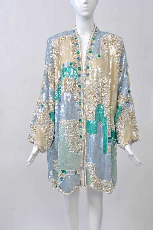 Extravagantly beaded and sequined 1980s 3/4 length coat in blue, ivory, and turquoise hues arranged in an abstract geometric configuration. Open front, wide sleeves, shoulder pads. Retailed by Lillie Rubin, a high-end boutique on New York's 57th St.