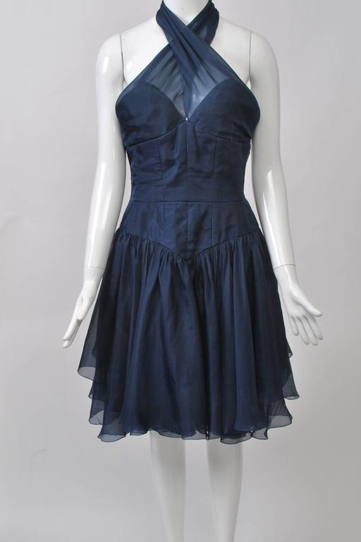 Chanel Boutique navy organza short cocktail dress with criss-cross halter neckline, bustier-style fitted bodice and fitted V-shape hip area. Dropped full skirt composed of several layers of the organza. Halter neck secured by 2 Chanel logo buttons.