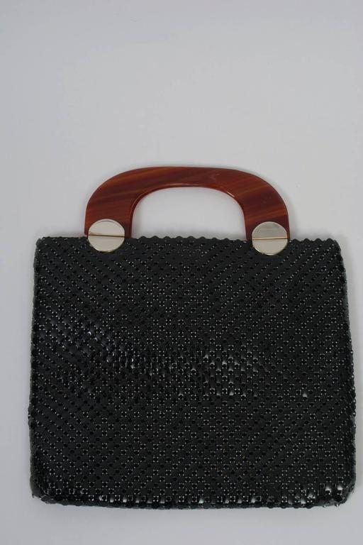 A rare modern design from Whiting & Davis, this 1960s tote ifeatures a large-gauge black mesh and tortoise shell handles with circular gold metal hinges, a motif repeated as a decorative touch on the front of the bag. Interior has side compartment