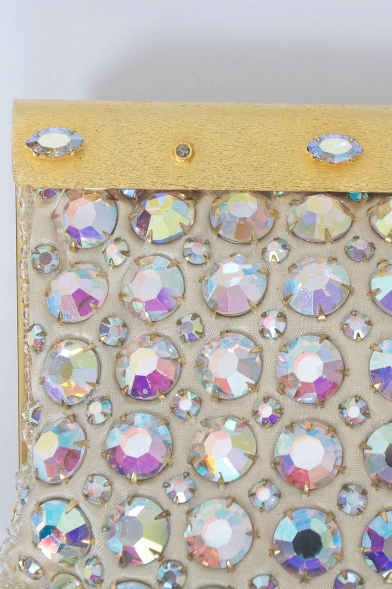 Glamorous evening clutch featuring large ABA rhinestones on a white ground. Satin finish gold metal hinged frame with matching rhinestones alternating in marquise and small rounds. Ivory satin interior with unused mirror in side comartment. Marked