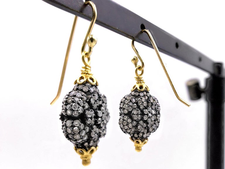 Drop Earrings handmade by jewelry designer Fern Freeman featuring shimmering round diamonds set on double-sided black rhodium-finished sterling silver elements wrapped in 22k yellow gold accenting.