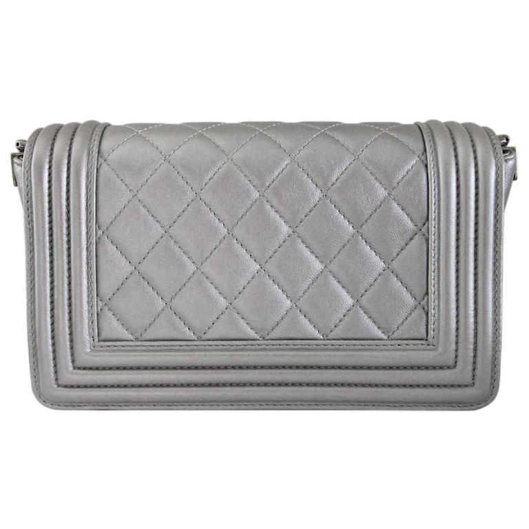 """Brand: CHANEL Style: Boy Bag Handles: Adjustable, Removable, Silver Calfskin and Stingray Cross Body Strap; 1.75"""" in width Measurements: (L) 7.9"""" x (W) 2.8"""" x (H) 4.7"""" Exterior Materials: Silver Calfskin Hardware & Lining: Ruthenium Hardware,"""