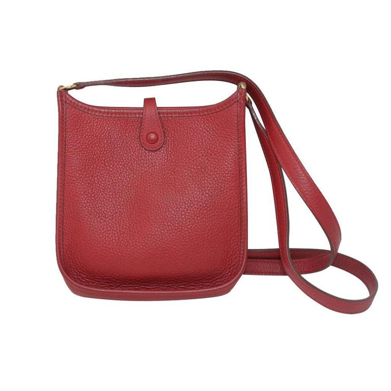 """Brand: Hermes Handles: Red Clemence Leather Shoulder Strap Drop: 23"""" Measurements: 6.75"""" x 2"""" x 7"""" Materials: Red Clemence Leather, Golden Brass Hardware Interior: No Pockets, No Zippers Red Suede Interior Lining Exterior: Perforated Leather"""