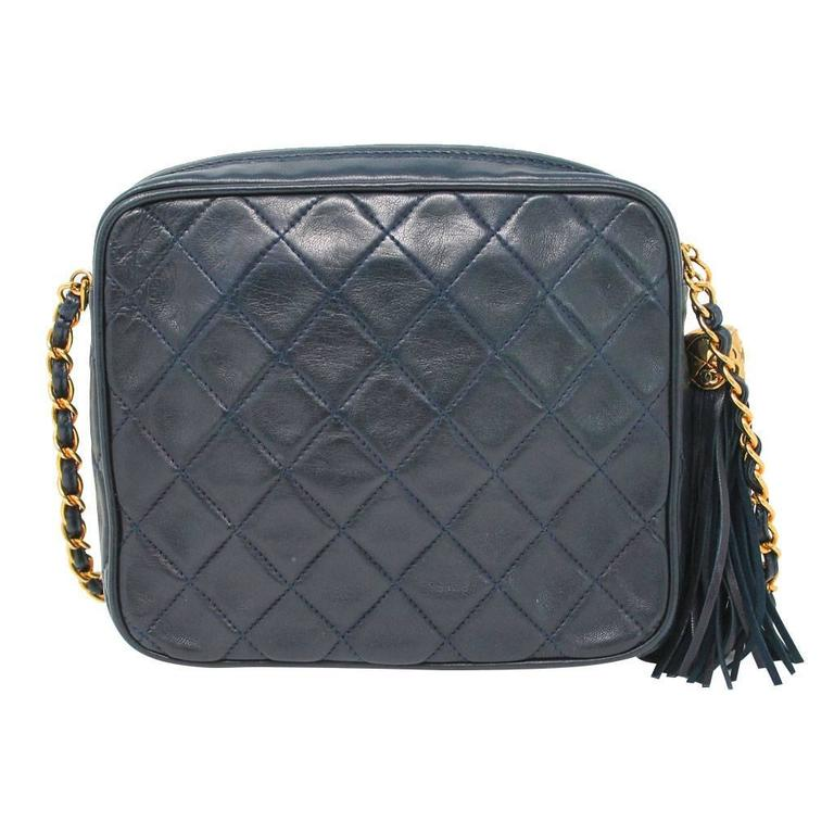 """Brand: Chanel Handles: Navy Lambskin Braided with Gold Chain Drop: 17"""" Measurements: 8"""" x 2.25"""" x 7"""" Materials: Navy Quilted Lambskin, Gold Tone Hardware Interior: Navy Lambskin Interior Lining, 1 Small Zipper Compartment with Navy Silk"""