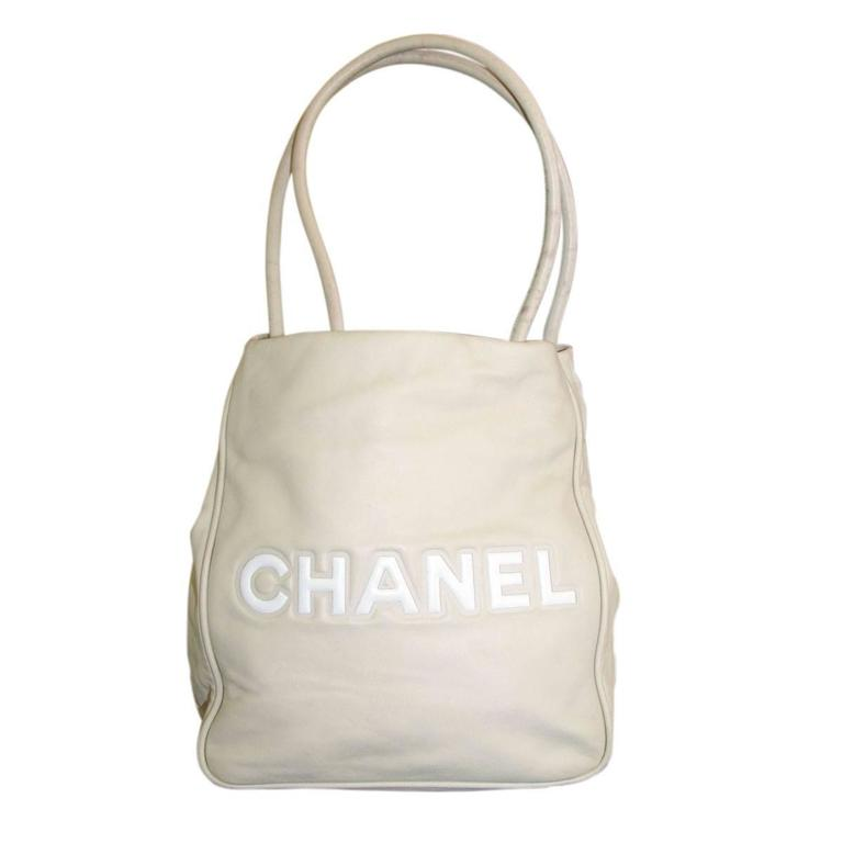 """Brand: Chanel Handles: Tan Stiff Lambskin Handles; Drop: 7.5"""" Measurements: 10"""" x 5"""" x 10.5"""" Materials: Tan and White Lambskin Leather, Light Gold Hardware Interior: Pink Beige Textile Interior Canvas, 2 Zipper Compartments Exterior: No Pockets"""