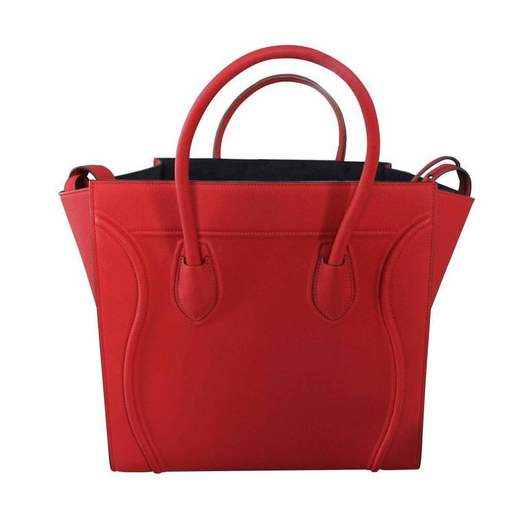 """Company: Celine Style: Luggage Tote Handles: Rolled Red Leather Handles; Drop: 4 inches Measurements: 11"""" in height x 13"""" in depth closed length: 11.75"""" open length: 21.5"""" Materials: Red Leather Hardware & Lining: Blueish-Purple-Gray Suede"""