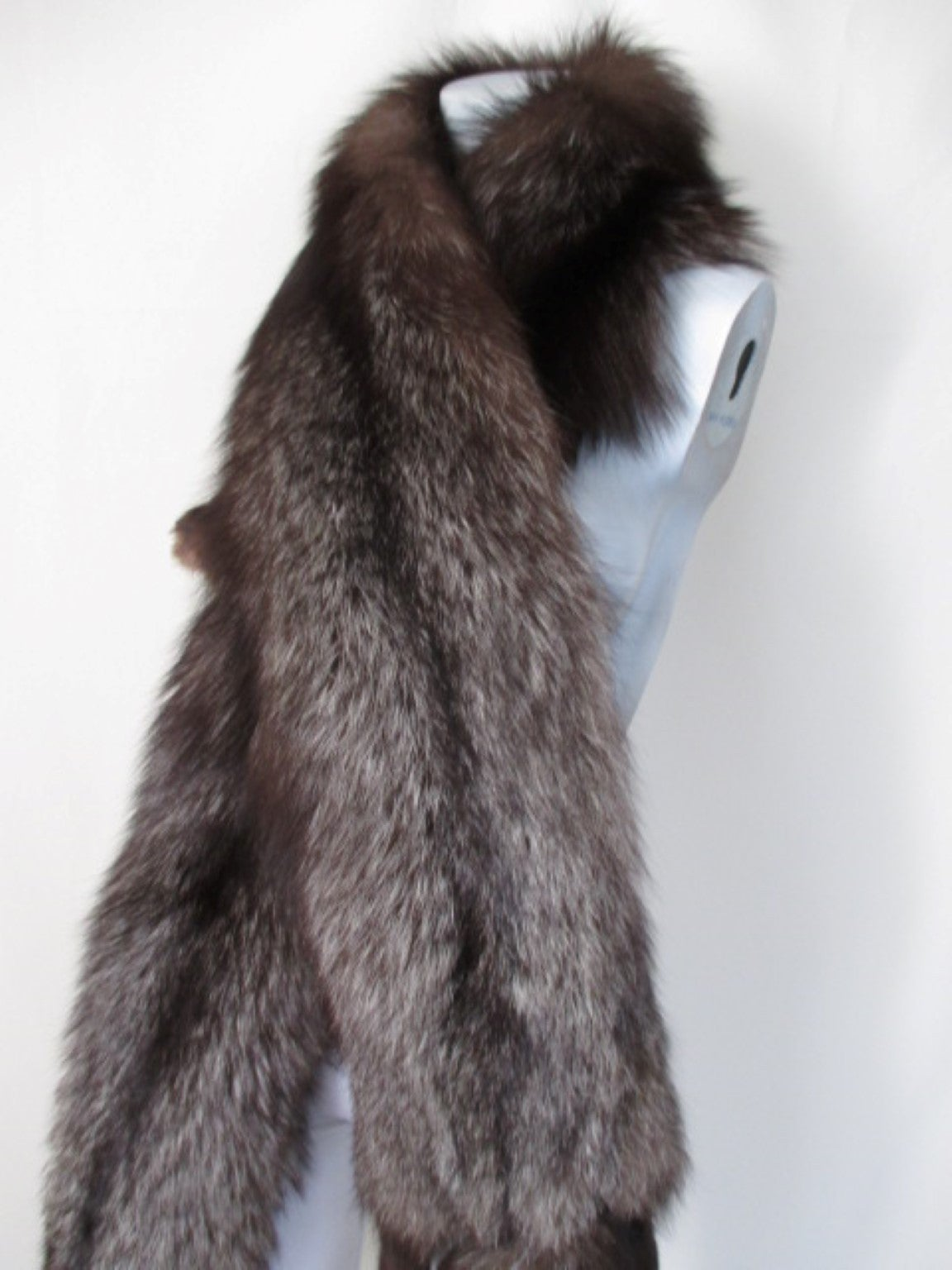 This luxurious vintage silver fox white tip tail long stole shawl wrap dates from the 20 century. It is made of fluffy plush soft supple silver gray blackish brown fox fur pelts with white tip tails. 