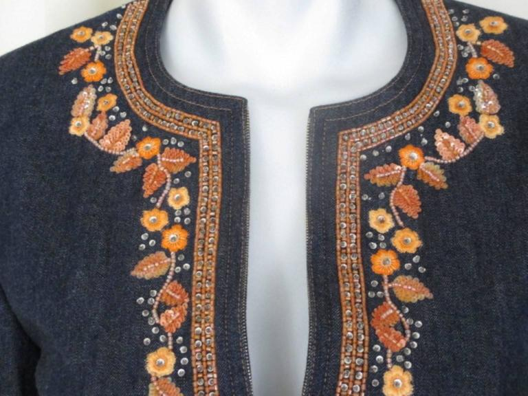 Escada jeans jacket is embroided with orange flowers and zipper closing.