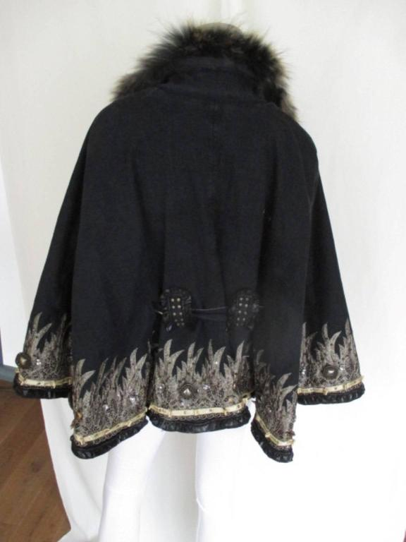 This cape is designed by Cobayashi. Material outside is 98% cotton/ 2% elasthane, Inside is soft material 60% polyester/ 40% acryl, which keep you warm. Its embroidered with stones and gold color fabric. The collar is made of fox fur. Belt is on 1