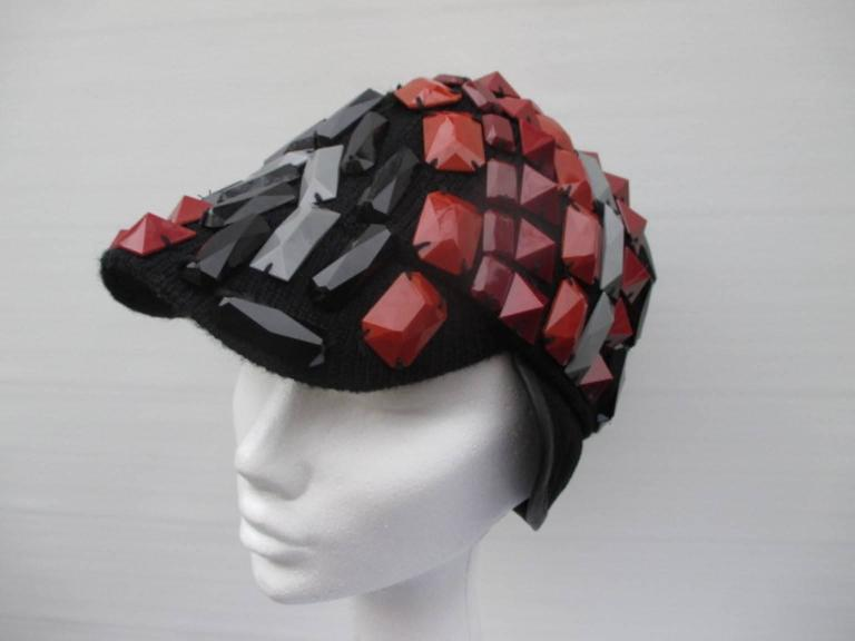 This hat is knitted and embroided with synthetic color studs. The side flaps are made of black suede leather. Its in excellent condition Size is 57 cm/22.44 inch