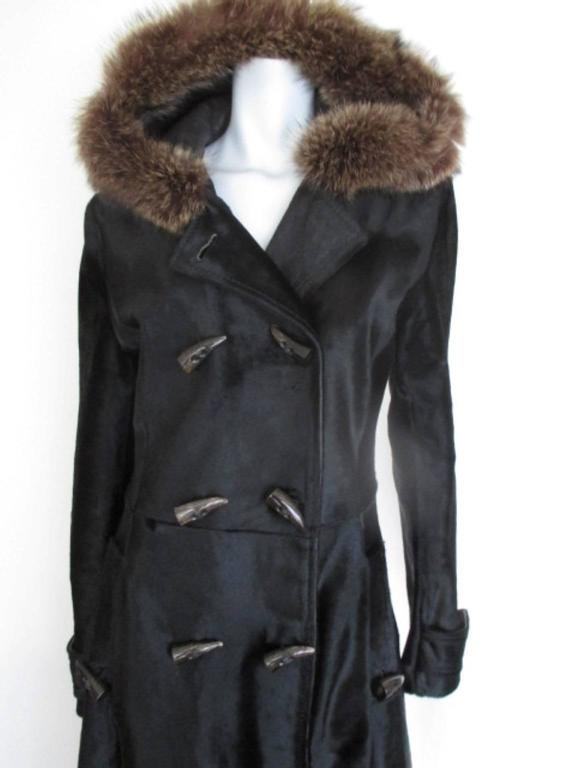 This coat is made of quality skin with a hood lined with soft calf skin leather and fur. It has 2 pockets and double brested with 8 buttons at front, 2 at the pockets and 2 at the sleeves. Its worn but in very good condition Size is Italian 46   EU