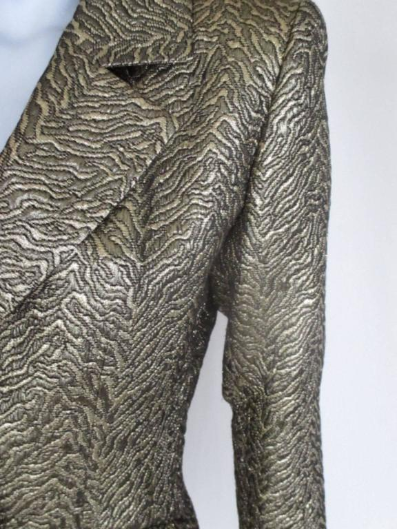 It's made of a gold metallic lamé textured tiger patterned animal brocade fabric. It has 2 pockets, 1 button at the front 3 at the sleeves and 2 extra buttons inside. The condition is excellent, almost new, only one time worn. Its from the 80's Rive