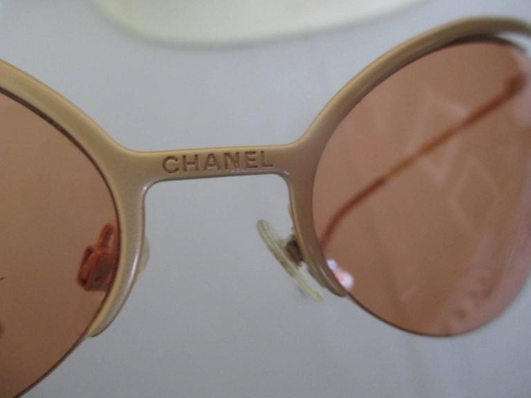 These super-stylized matte gold frame sunglasses have rimless oval orange color lenses and is very light to wear. CC gold metal logos on the bottom of the arms, Chanel engraved on the nose bridge and lenses Its in excellent vintage condition with a