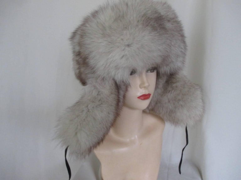 This hat is made of very soft fox fur trimmed with black leather. The ear flaps are much longer, so that the fur is guaranteed to protect your face and neck from the cold wind. size 58 cm / 22.83 inch