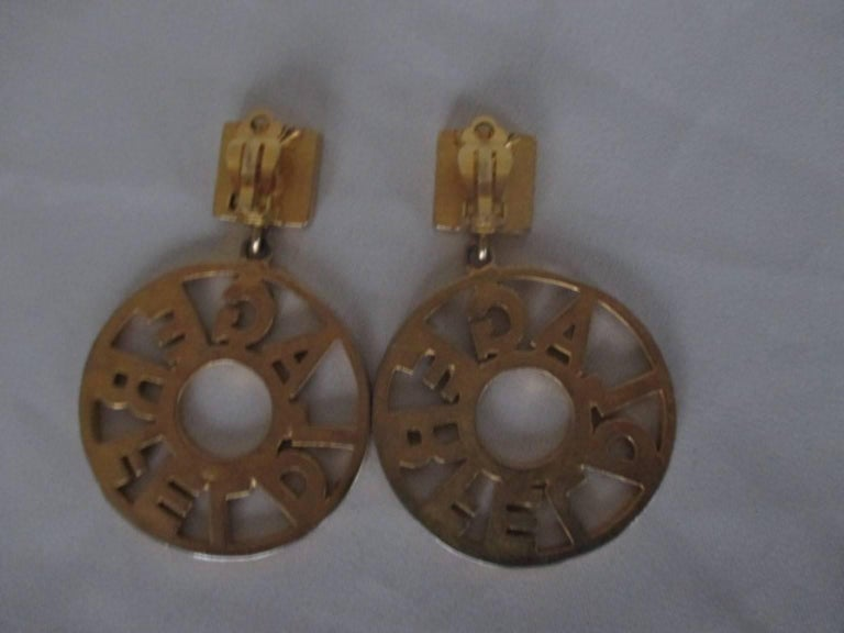 These vintage gold tone hoop earrings are 5 cm diameter and closes with a clip. Signed KL