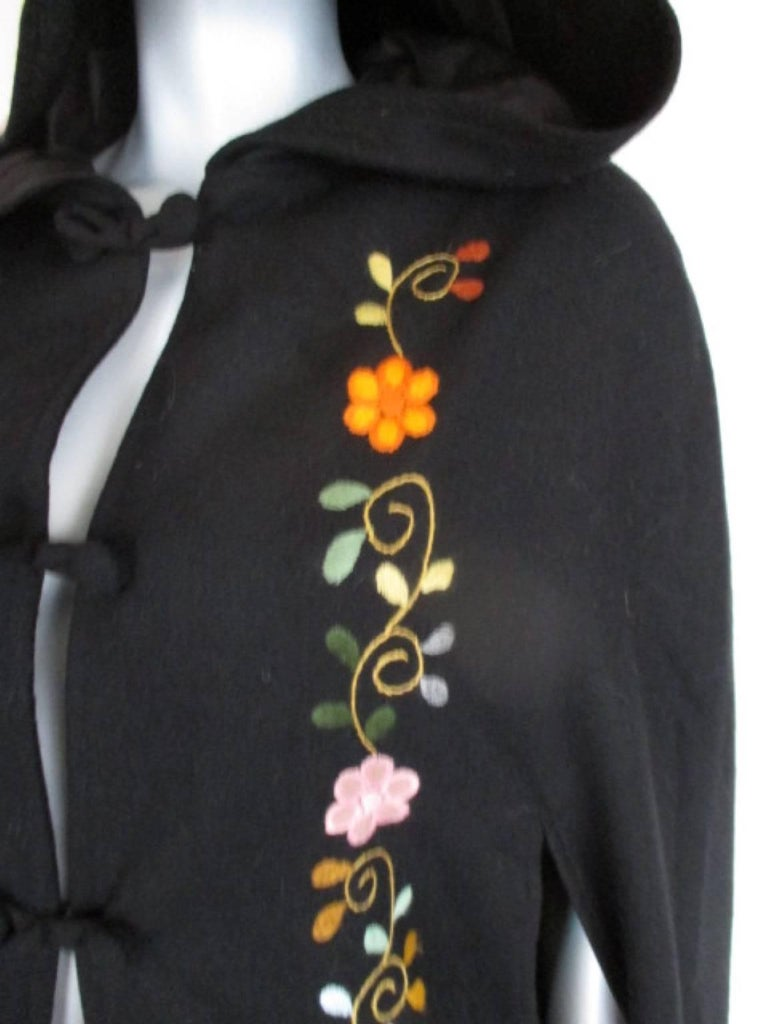 This beautiful cape is embroided with flowers in the front, back and at the hood. Its in good vintage condition. one size Please note that vintage items are not new and therefore might have minor imperfections.