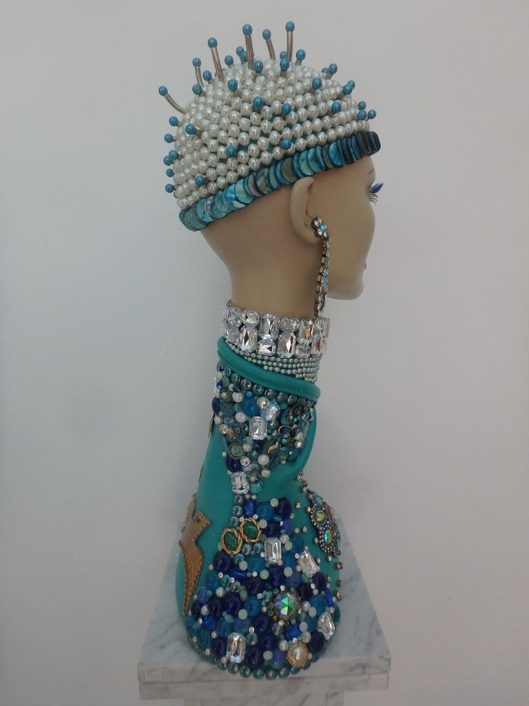 Astonishing sculpture, a wig head from fashion house Pierre Balmain decorated with, stones, brooches and other fashionable ornaments. Artist: L. van Santen Sizes 45 cm x 26 cm