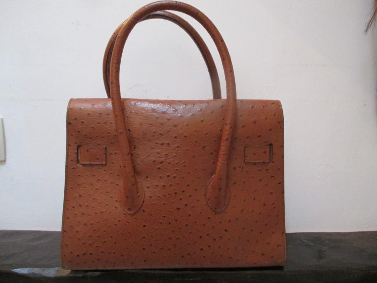 Brown/cognac embossed ostrich leather bag with gold hardware. Lining is leather with 1 zipper pocket good vintage condition with some wear. size; 24.5cm  x 31.5cm  x 12 cm Please note that vintage items are not new and therefore might have minor