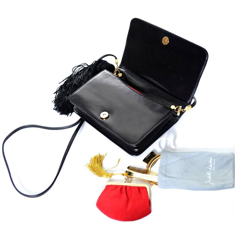 This is a vintage black patent leather Judith Leiber handbag with a side tassel and 6 brass animals and colored stones on the front.  You can carry this bag as a clutch or a shoulder bag. The bag has a detachable shoulder strap with a 19