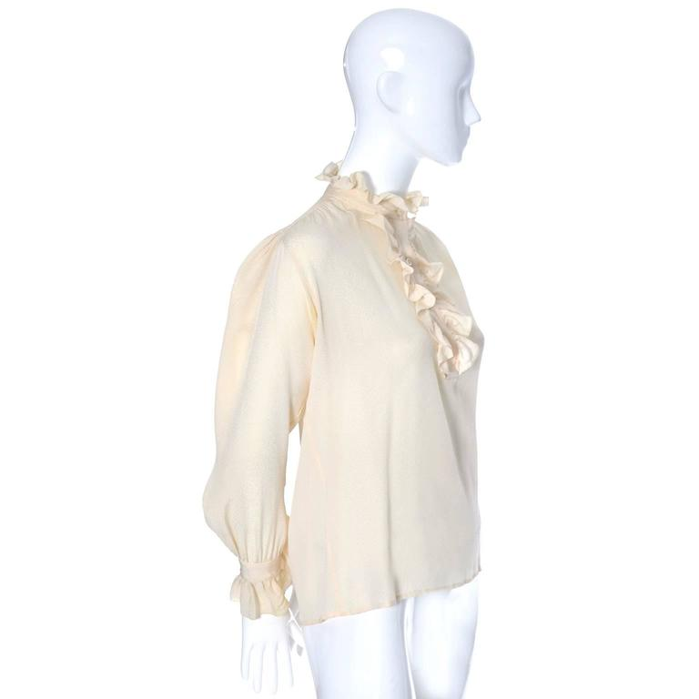 This is a pretty vintage silk blouse from Yves Saint Laurent.  This vintage blouse has the YSL Rive Gauche label and was made in France in the 1970's.  There is a pretty ruffle at the collar, on the cuffs, and around the buttons on the bodice. The