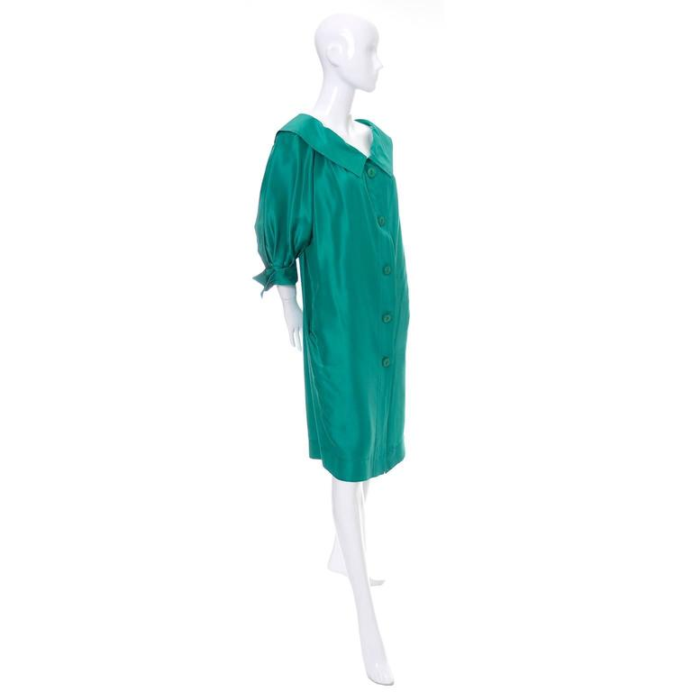 This is a late 1970's vintage YSL green silk dress with buttons up the front.  The dress has side pockets, pretty detailed cuffs on the 3/4 length puffed sleeves, and is labeled a size 38 (Approximately a US size 6). This dress was made in France